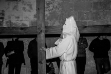 A hooded penitent carries a cross during the Good Friday procession. Xaghra, Malta - March 25, 2016